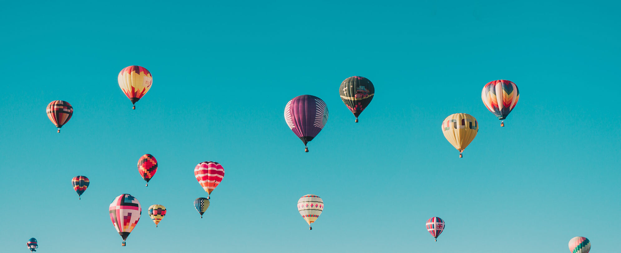 Bright blue sky with different color hot air balloons