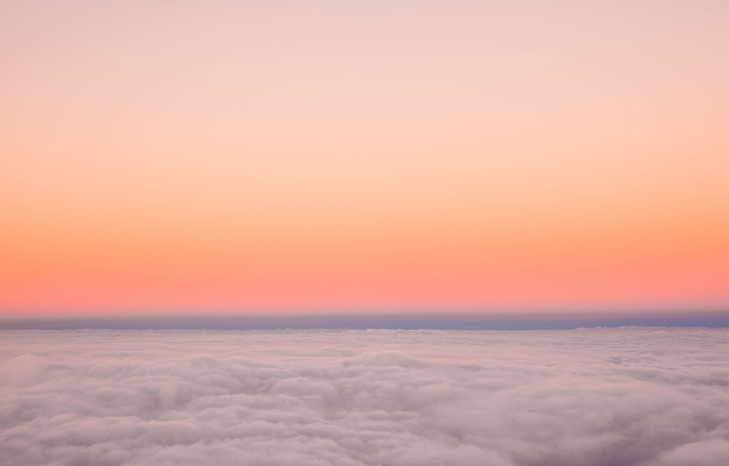 An orange, pink and purple sunset sky from above the clouds
